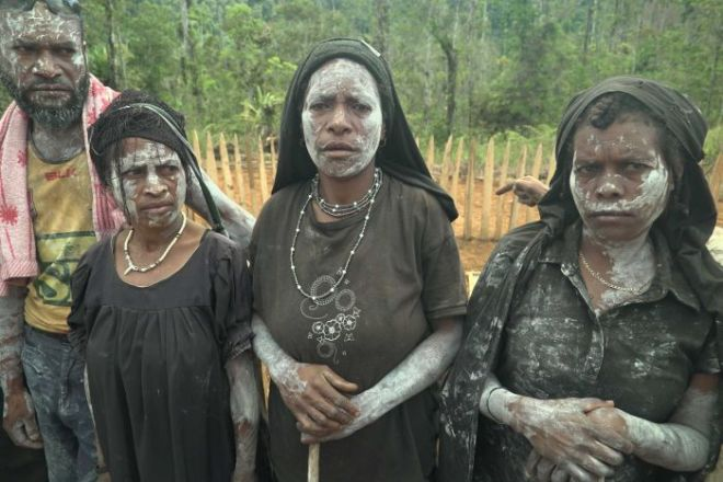 Three women and one man stand in a row with their faces painted white, mourning their lost relatives