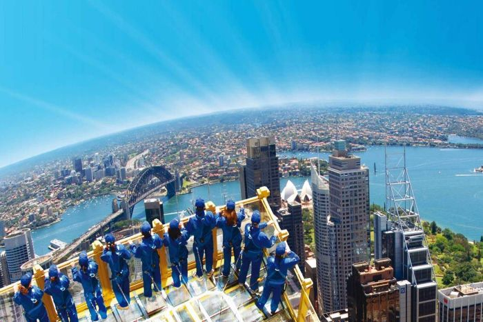 People stand on a glass platform high above the city, overlooking Sydney harbour.