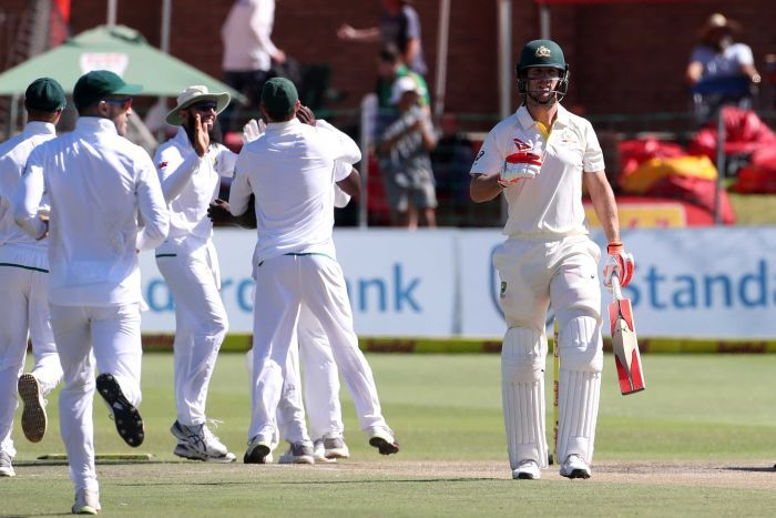 Mitchell Marsh walks off as South Africans celebrate behind him.