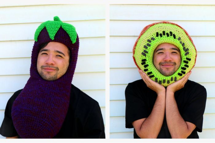 A young man in a crocheted eggplant hat and crocheted kiwi hat.