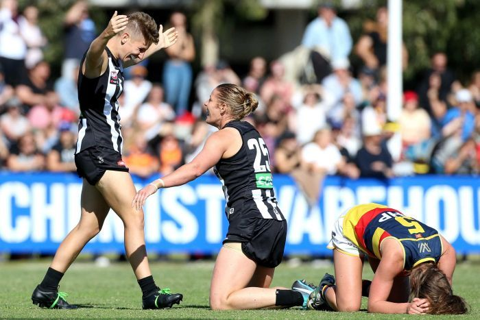 Collingwood players celebrate as Adelaide players despair