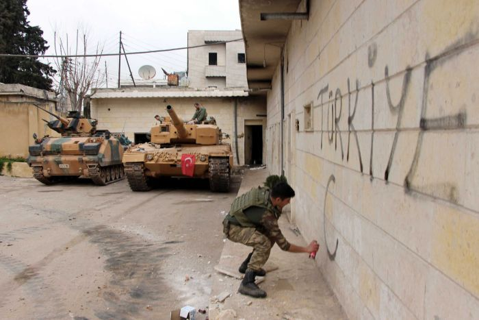 "A Turkish soldier writes ""Turkey"" on a wall, near to tanks in position"