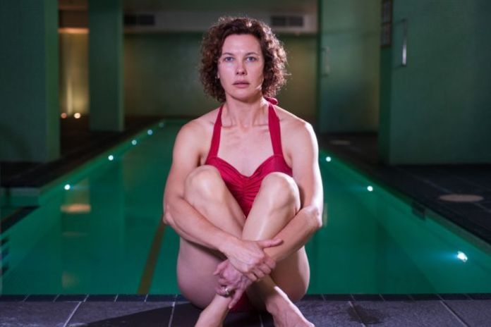 Mid-shot of performed Tiffany Lyndall Knight sitting upright with arms held against legs in front of a dimly lit indoor pool.