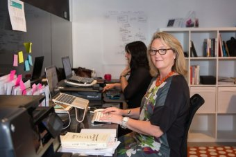Michelle Gallaher sits at a desk in an office