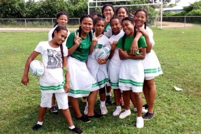 Medium shot of a group of girls posing for the camera on a playing field.