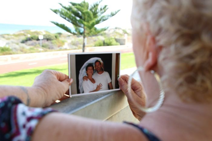A woman stands on a balcony holding a photograph of herself and son while looking out to the ocean.