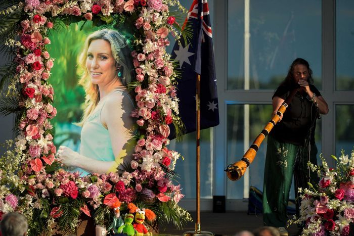 A photo of Justine Damond Ruszczyk is seen with flowers around it and a lady playing a didgeridoo in the background.