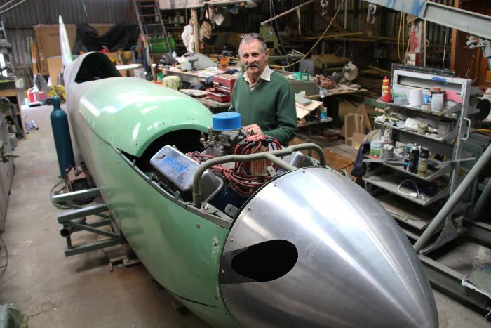 Rod McNeill stands at the side of the spitfire aeroplane he is constructing.