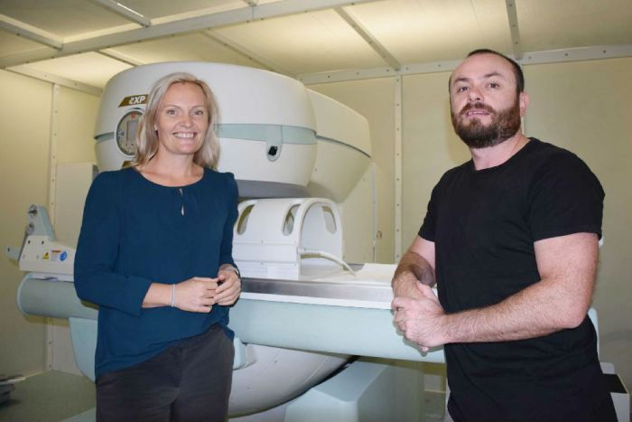 A woman and man stand and smile in front of a large bulky white MRI machine