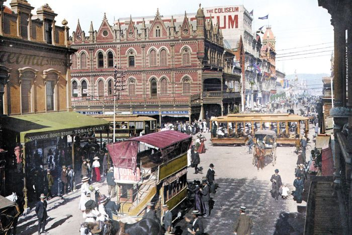 A colourised photograph of the busy Beehive Corner, in Adelaide, 1909, featuring horse-drawn carriages and people wearing hats.