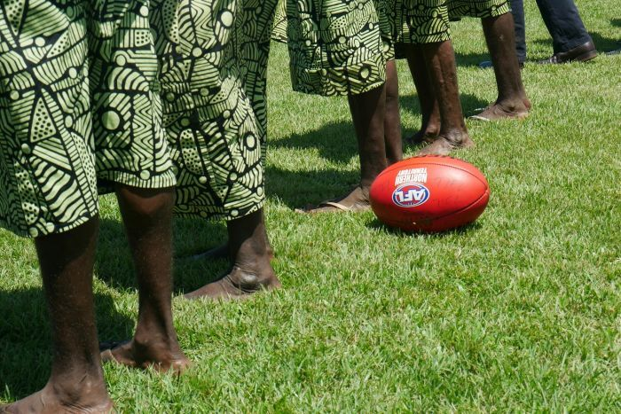 Indigenous men and women stand on a football field next to an AFL ball.