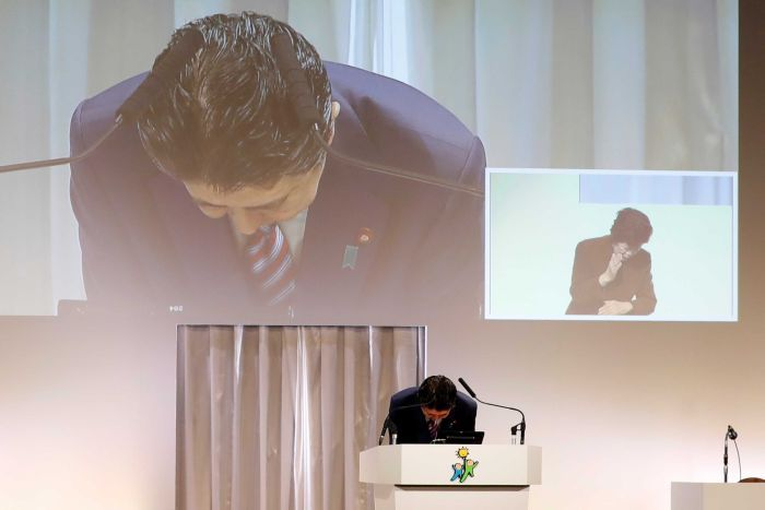 Shinzo Abe is seen bowing as he stands on a podium, behind him we see the projection of his image and a woman bowing.