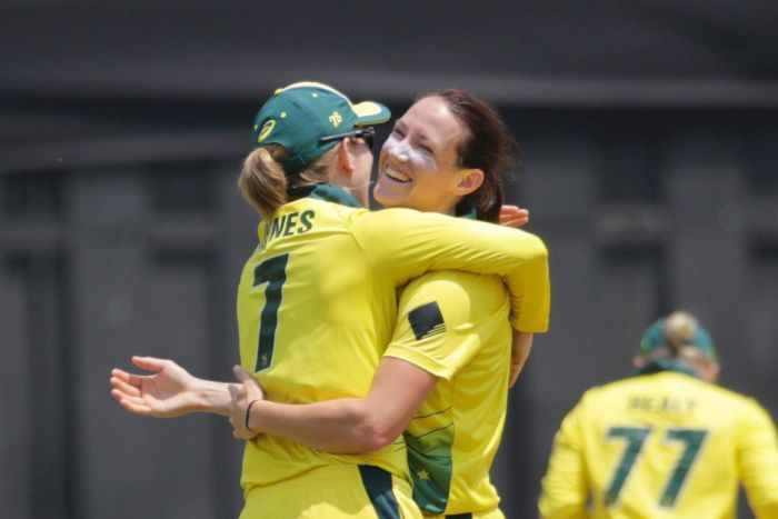 Two female cricketers embrace to celebrate a wicket in a T20 match against India in Mumbai