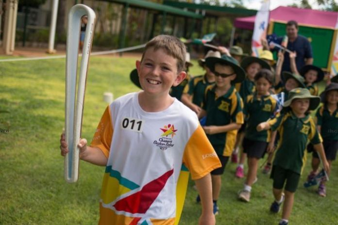 An 11-year-old boy carries the Queen's Baton ahead of the Commonwealth Games on the Gold Coast