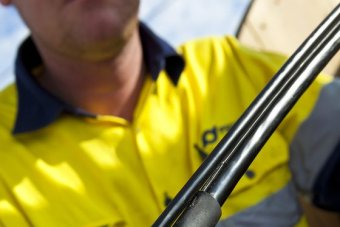 Hands hold an optic fibre wire during installation of Tasmania's National Broadband Network