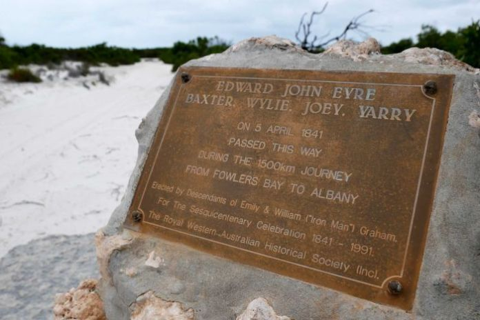 A rusty metal plaque bolted to a rock in white sandy dunes.