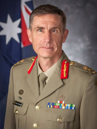 Angus Campbell, wearing his Army uniform, sits in front of a grey background and Australian flag.