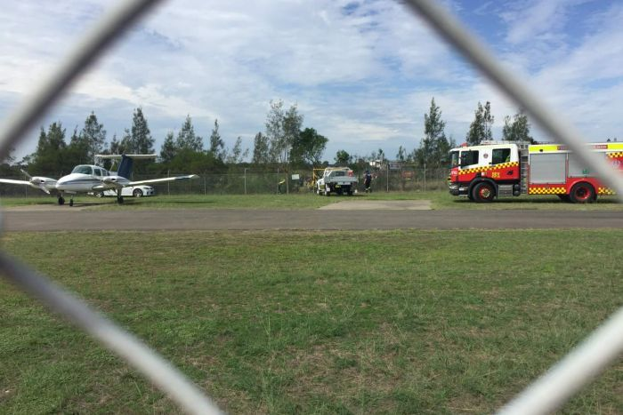 Several people, and emergency service vehicles in the distance, surrounded by trees.