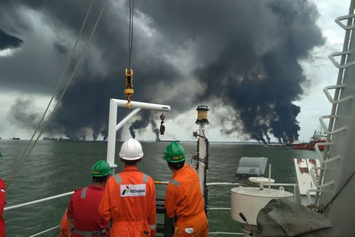 Three workers look out at smoke rising from the ocean.