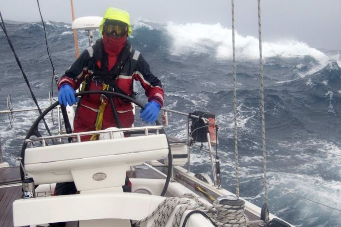 Sailor at helm of yacht in large swell.