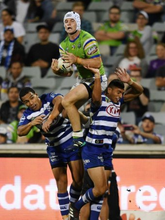 Raiders captain Jarrod Croker leaps above two Bulldogs players to catch a kick