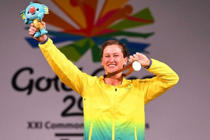 Weightlifter Tia-Clair Toomey lifts her medal and games mascot
