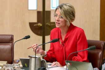 Kristina Keneally asking a question in an Estimates committee. She's wearing a red blouse and clear glasses.