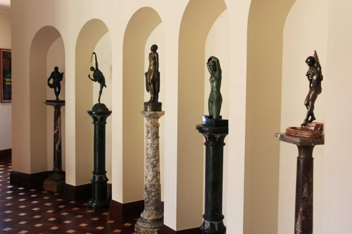 Bronze statues in archways inside a home.