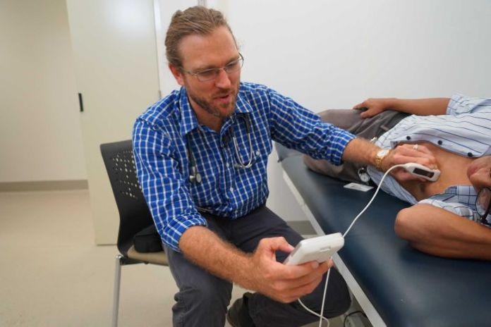 Dr Josh Francis using the hand-held echocardiography device on a patient.