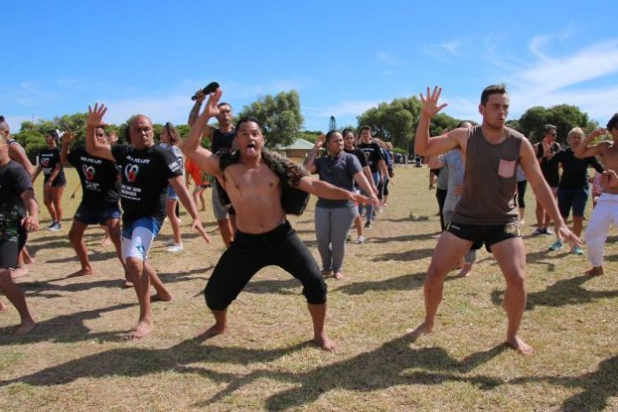 A group of people perform the haka in a park.