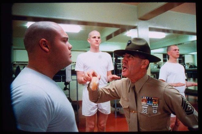 Still from Full Metal Jacket showing Ermey as the Gunny holding a bread role and berating a male recruit in a dormitory