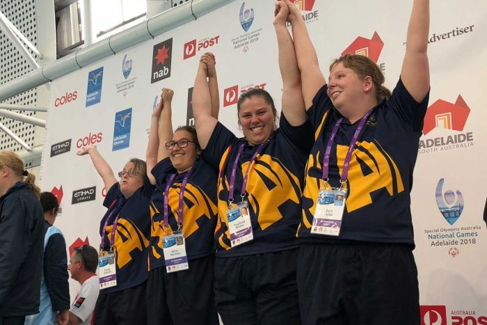 South Australian swimming team put their hands up on the podium after winning gold.