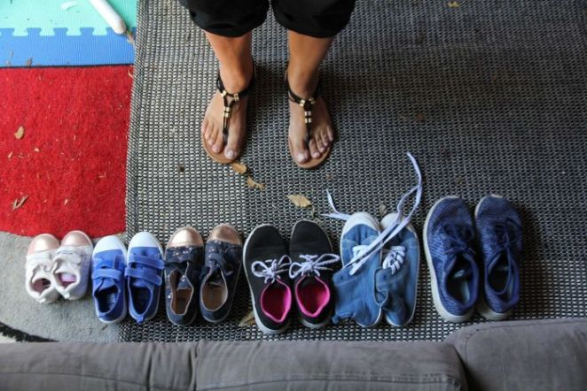 Six pairs of shoes are lined up next to each other with grandma's feet facing them