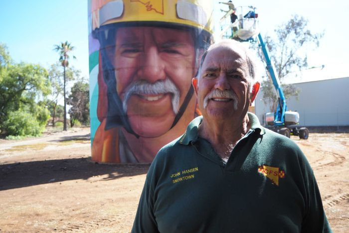 White male with big moustache stands in front of brightly painted water tower, with artist painting on lifter in background.