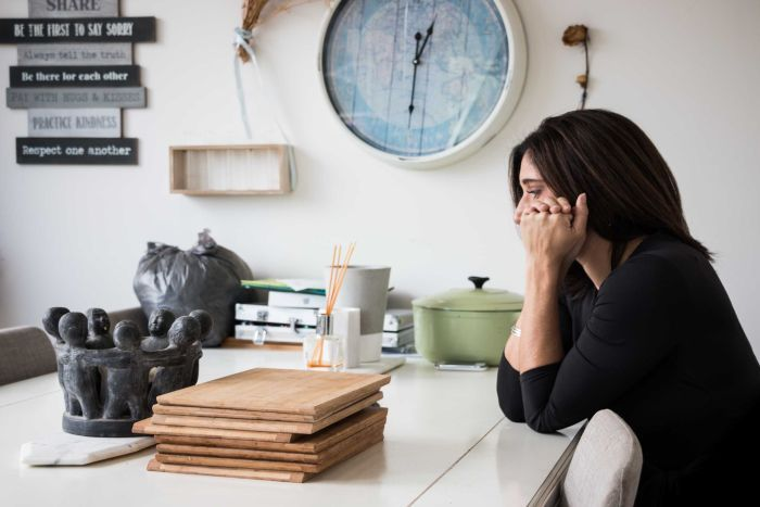 A woman sits at a desk, clasping her hands to her head.