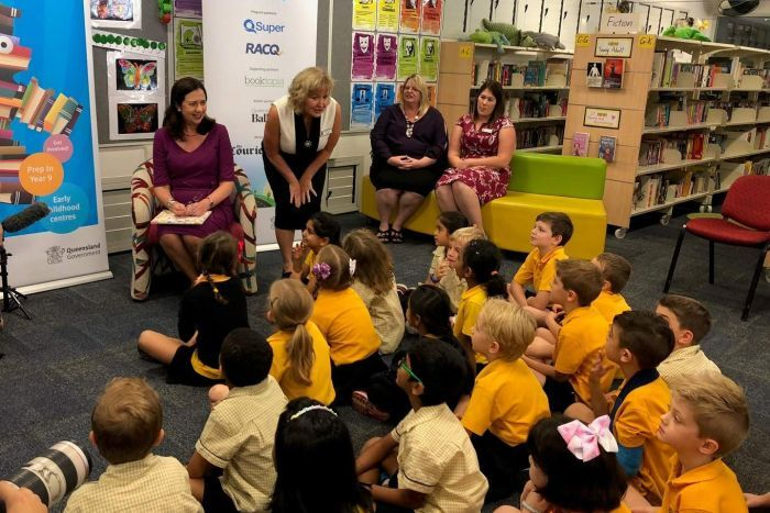 Premier Annastacia Palaszczuk and teachers in front of primary school children in a school library.