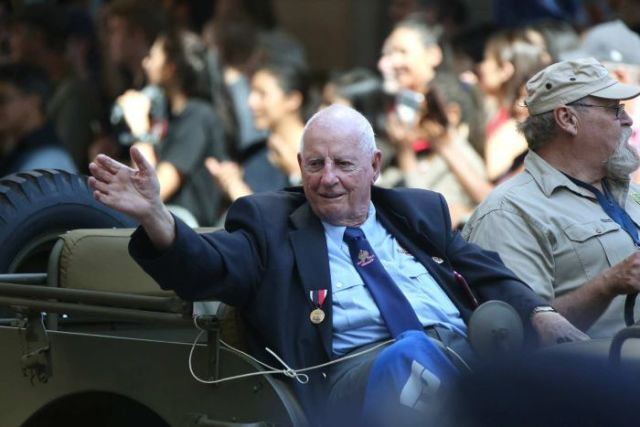 A veteran waves to the crowd from a military jeep in the Brisbane Anzac Day march on April 25, 2018.