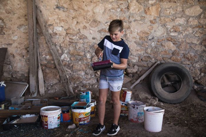 A young boy stands in a shed surround by tins of paint and holding a paint pallet.