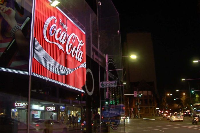 "A neon-lit ""Enjoy Coca Cola"" sign on a street at night."