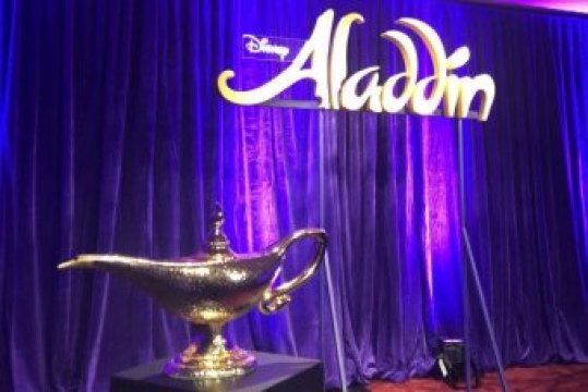 Genie's lamp placed in front of an Aladdin backdrop.