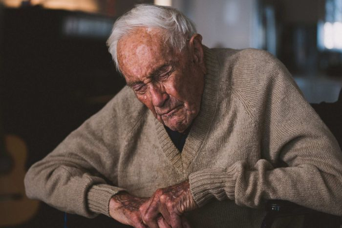 An elderly man in a tanned cardigan sits in a chair with his eyes closed against a dark background.