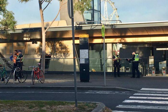 Police officers stand outside North Melbourne station.