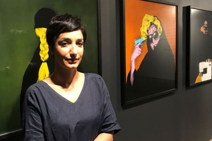 A woman stands in front of artwork