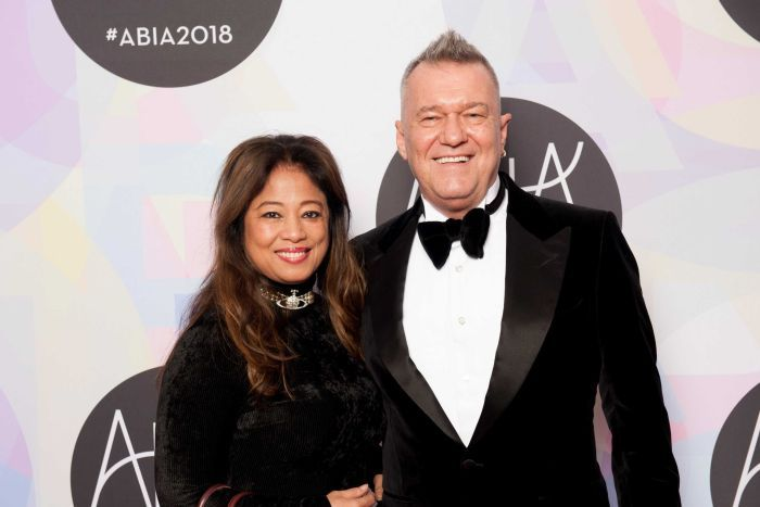 Barnes and Mahoney stand, smiling and wearing formalwear, arm in arm in front of a pastel coloured media wall.