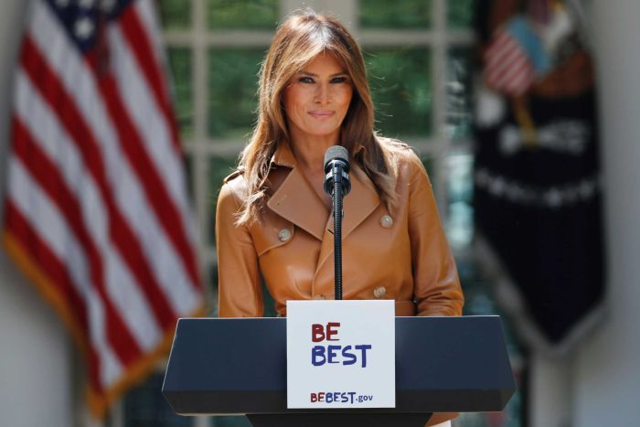 Melania Trump smiles, standing behind a lectern with the slogan Be Best written on it, with american flags behind her