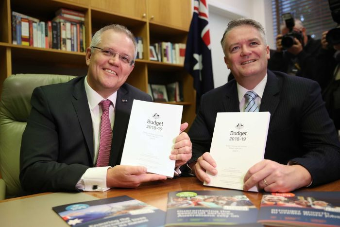 Morrison and Cormann each hold a Budget book, sitting at a table smiling at the cameras.
