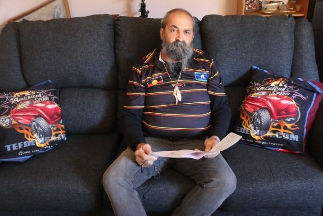 Garry Smith sits on his lounge, holding documents which he claims have whitewashed his family history.