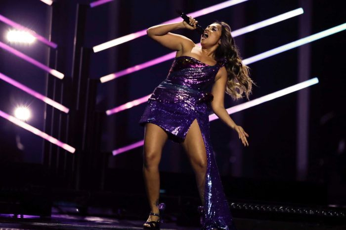 Singer Jessica Mauboy leaning back while singing into a microphone and wearing a purple dress