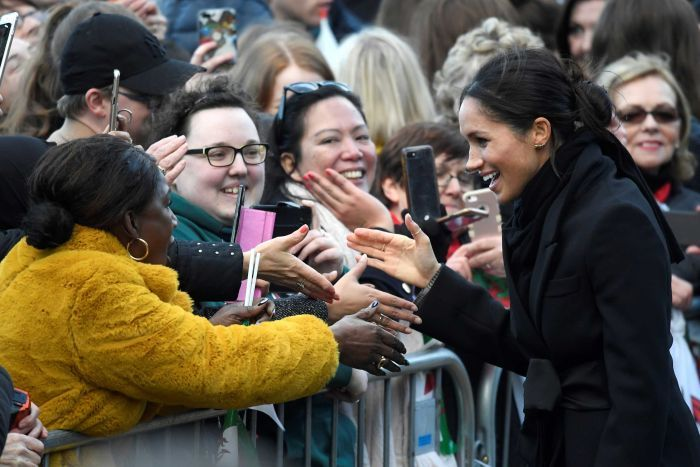 Meghan Markle talks to fans taking photos with their phones.