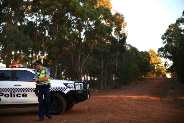 A police officer stands on an empty gravel road outside Margaret River.